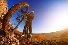 Low angle view of cyclist riding mountain bike on rocky trail at sunrise Stock Photography