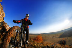 Low angle view of cyclist riding mountain bike on rocky trail at sunrise Royalty Free Stock Photos