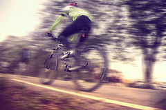 Low angle view of cyclist riding mountain bike, Vintage style. Low angle view of cyclist riding mountain bike with speed effect Stock Photo