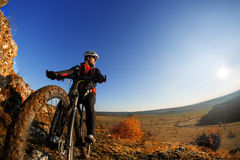 Low angle view of cyclist standing with mountain bike against bright sun and blue sky. Stock Photo