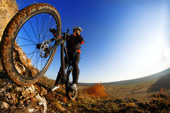 Low angle view of cyclist standing with mountain bike against bright sun and blue sky. Stock Images