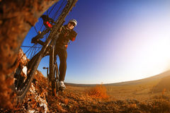 Low angle view of cyclist standing with mountain bike against bright sun and blue sky. Royalty Free Stock Photography