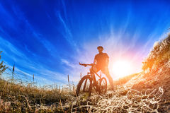 Low angle view of cyclist standing with mountain bike on trail at sunrise. Attractive sportsman in the sportwear and with helmet. Horizontal photo and fisheye Royalty Free Stock Image