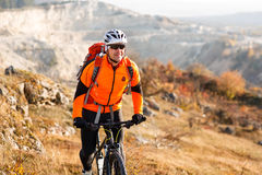 Low angle view of cyclist standing with mountain bike on trail at sunset Royalty Free Stock Photography