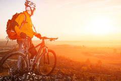 Low angle view of cyclist standing with mountain bike on trail at sunset Royalty Free Stock Photo