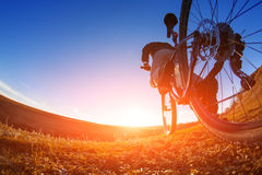 Low angle view of cyclist standing with mountain bike on trail at sunset. Fisheye. Beautiful landscape with blue sky and hill. Travel in the countryside. Sport Royalty Free Stock Photography