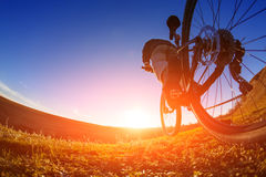 Low angle view of cyclist standing with mountain bike on trail at sunset. Fisheye. Beautiful landscape with blue sky and hill. Travel in the countryside. Sport Royalty Free Stock Image