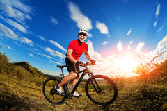Low angle view of cyclist standing with mountain bike on trail at sunset Stock Image