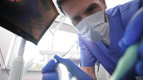 Low angle view of dentist doing his work. In dentist`s clinic stock footage