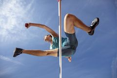 Low angle view of determined male athlete jumping over a hurdles royalty free stock photos