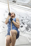 Low angle view of determined man climbing rope in crossfit gym stock photography
