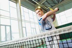 Low angle view of determined young man playing tennis indoor Stock Images