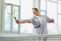 Low angle view of determined young man playing tennis indoor Royalty Free Stock Photography