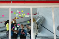 Business people discussing over sticky notes on glass wall in a modern office. Low angle view of diverse business people discussing over sticky notes on glass royalty free stock image