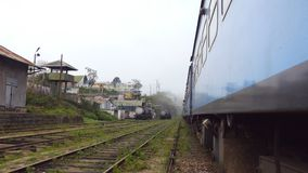 Low angle view from doors of old blue train crossing small village in morning. Passenger railway transport moving. Through beautiful scenic countryside. Concept stock footage