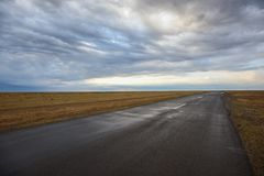 Low angle view of empty road under stormy dramatic sky Royalty Free Stock Photo