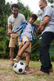 Low angle view of family playing soccer in yard Royalty Free Stock Image