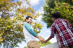 Low angle view of father and son holding hands. While standing against tree in yard Stock Photos