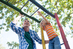 Low angle view of father and son playing on jungle gym royalty free stock image