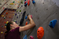 Low angle view female athlete climbing wall Royalty Free Stock Images