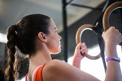 Low angle view of female athlete holding gymnastic rings Royalty Free Stock Photography
