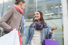 Low angle view of female friends with shopping bags looking at each other against store Royalty Free Stock Photos