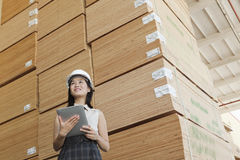 Low angle view of female industrial worker holding tablet PC with stacked wooden planks in background Royalty Free Stock Images