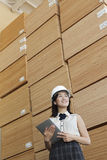 Low angle view of female industrial worker holding tablet PC with stacked wooden planks in background Royalty Free Stock Image