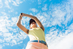 Female professional player holding up the iron club while playin. Low-angle view of a female professional player holding up the iron club with concentration for Royalty Free Stock Images