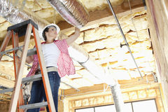 Low angle view of female worker working on incomplete ceiling Stock Photo