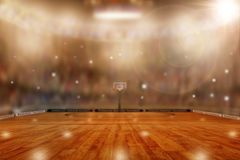 Basketball Arena With Copy Space. Low angle view of fictitious basketball arena with flashes from sports fans in the stands and lens flare effect. Focus on Royalty Free Stock Photography