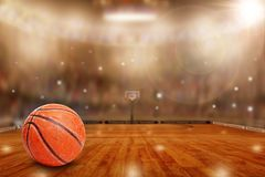 Basketball Arena With Ball on Court and Copy Space. Low angle view of fictitious basketball arena with flashes from sports fans in the stands and lens flare Royalty Free Stock Photo