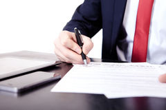 Low angle view of the fingers of a man writing on a document with a fountain pen conceptual of communication Royalty Free Stock Images