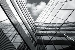 Low angle view of flying airplane over modern architecture build stock photos