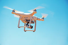 Low angle view of flying drone. Low angle view of drone with camera flying against the sky Stock Photo