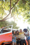 Low angle view of friends reading map at campsite Royalty Free Stock Photography