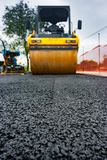 Roadroller low angle view. Low angle view in front of a roadroller on a newly laid asphalt. Close focus, so any small item can be placed on the asphalt to be stock image