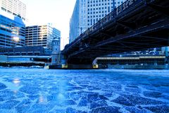 Low-angle view of a frozen Chicago River underneath the Frankly Street bridge on a blue and frigid morning. In January stock photos