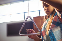 Low angle view of girl playing triangle stock image