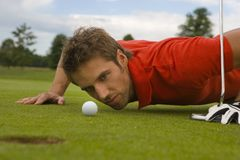 Low angle view of a golfer lining up a short putt. Royalty Free Stock Photos