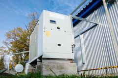 Low angle view of the gray industrial cooling unit standing outdoor on the ground near to the modern of the factory building. Low angle view of the industrial Stock Image