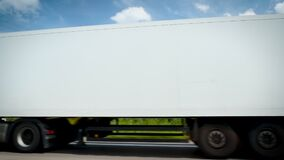 Low angle view of green Mercedes Benz Actros truck cargo trailer with white