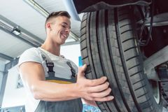 Low-angle view of the hand of a skilled auto mechanic holding a tire Royalty Free Stock Image