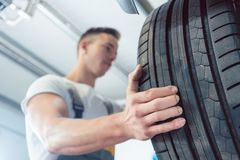 Low-angle view of the hand of a skilled auto mechanic holding a tire. Low-angle view of the hand of a skilled auto mechanic holding a new high-quality tire Royalty Free Stock Images