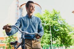 Low angle view of handsome smiling young man. Standing with bicycle and looking away on street stock photography
