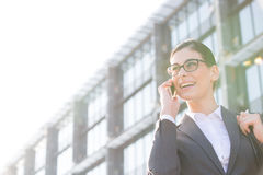 Low angle view of happy businesswoman using cell phone outside office building Stock Image