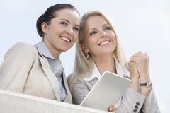 Low angle view of happy businesswomen with digital tablet looking away against clear sky Royalty Free Stock Images