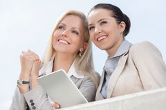 Low angle view of happy businesswomen with digital tablet looking away against clear sky Stock Photo