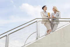 Low angle view of happy businesswomen discussing while standing by railing against sky Stock Photos