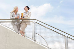Low angle view of happy businesswomen discussing while standing by railing against sky Royalty Free Stock Photos